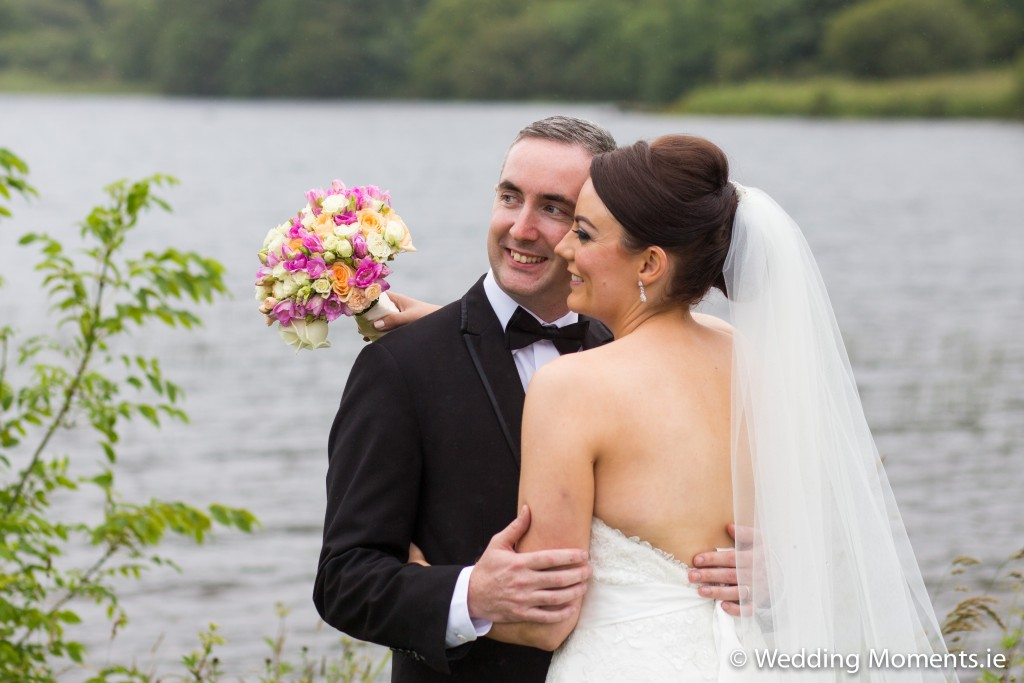 bride and groom smiling with lough talt lake in the background in sligo