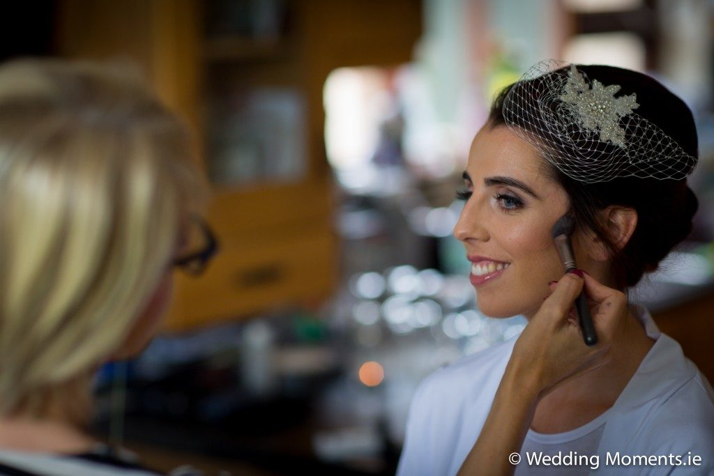 bride getting makeup done by makeup artist