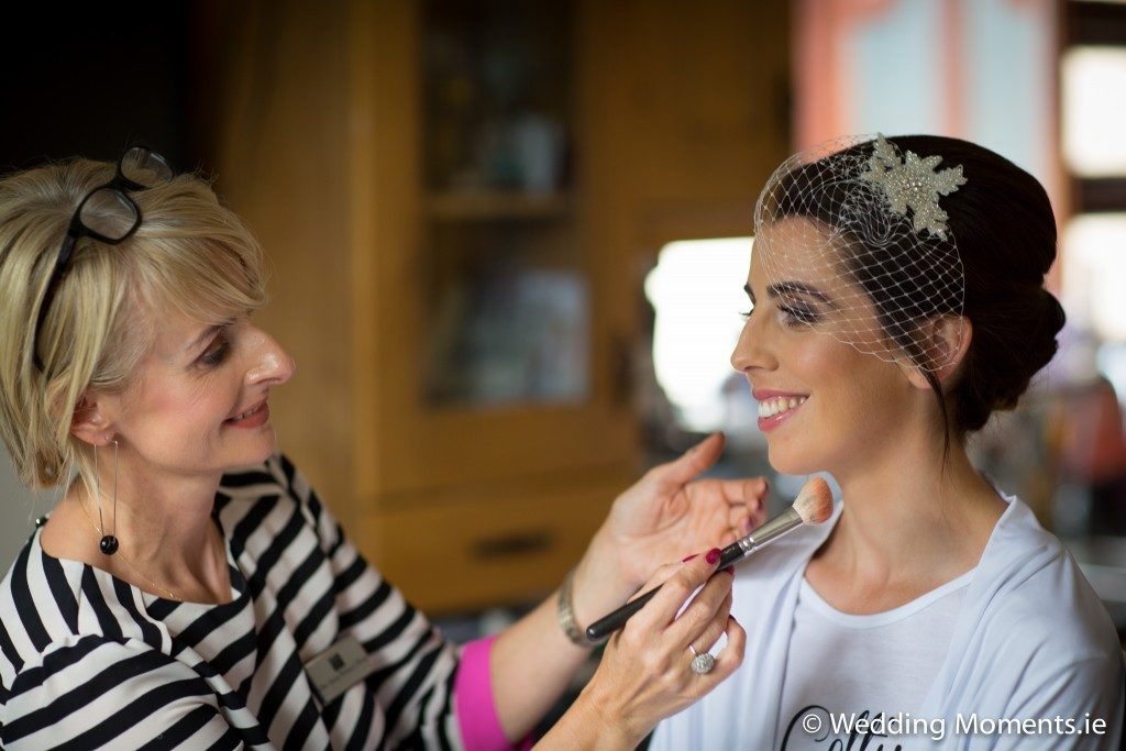 bride smiling getting her makeup applied