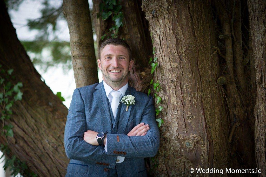 groom standing at tree