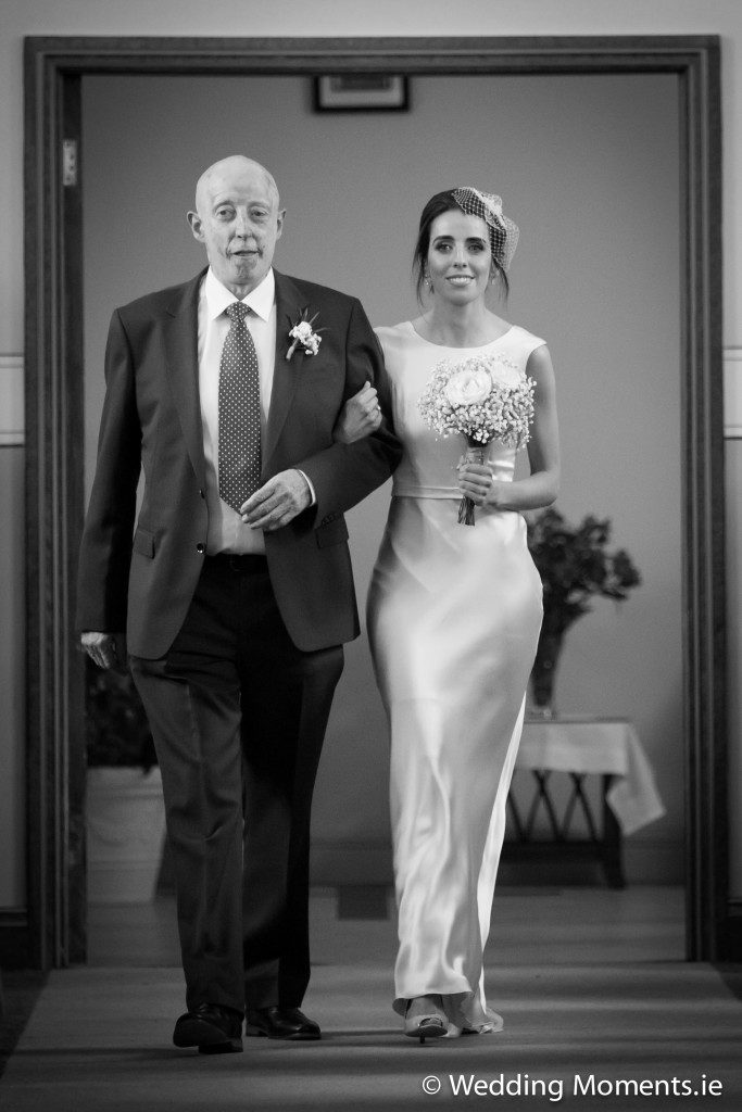 closeup photo of bride with her dad walking up the aisle of the church