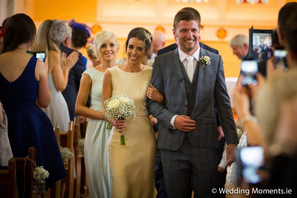 closeup of bride leaving church with groom