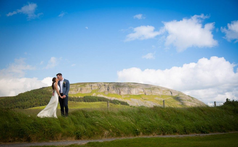 bride and groom standing in front of epic mountain