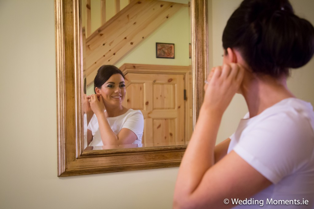 bride looking at her wedding ring in a mirror smiling
