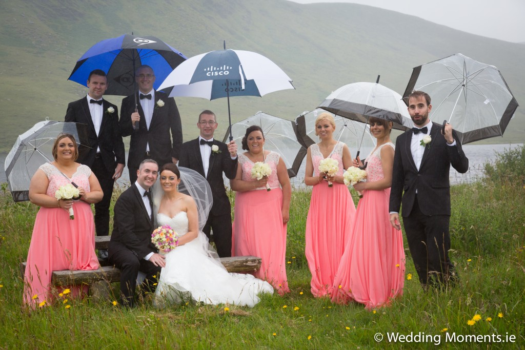 bridal party standing in the rain with umbrellas