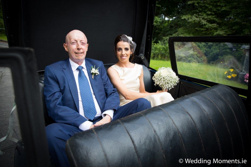 bride in wedding car with her dad nice and relaxed