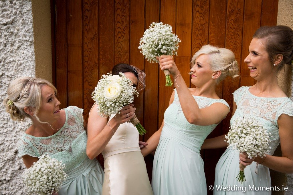 funny picture of bridesmaids swatting bee with flowers