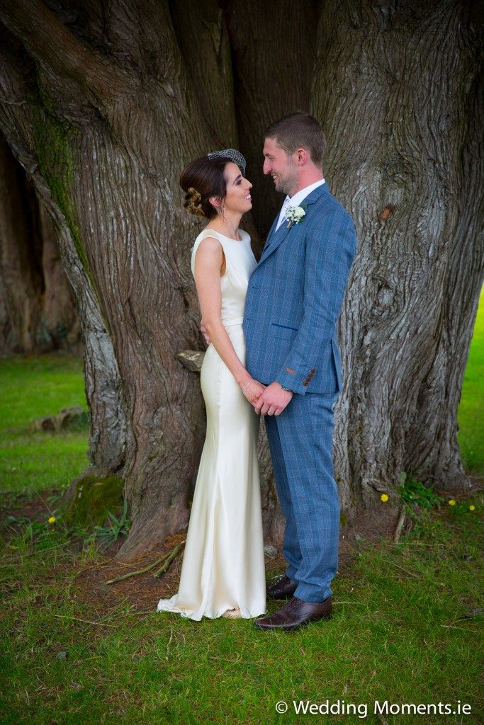 bride and groom posing at tree