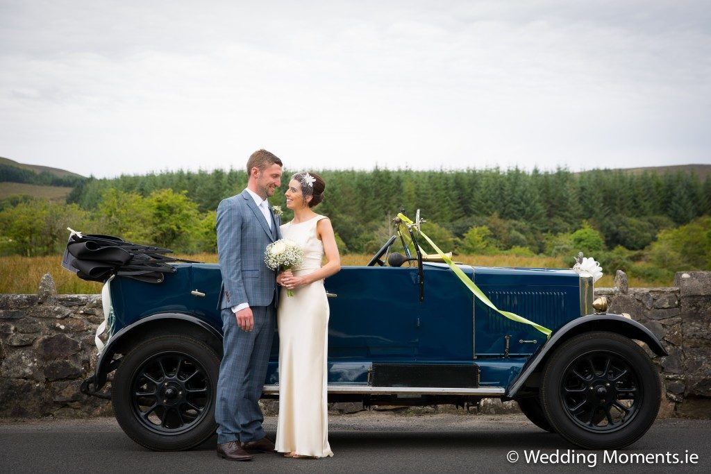 bride and groom standing at wedding vintage car