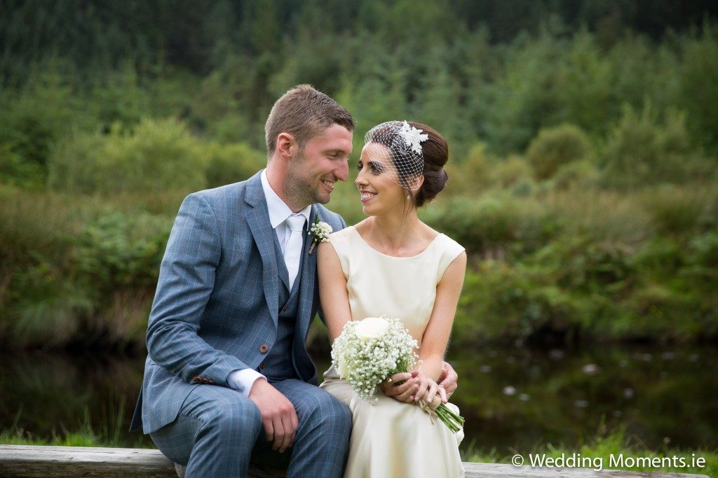 bride and groom sitting on bench with the river in the background