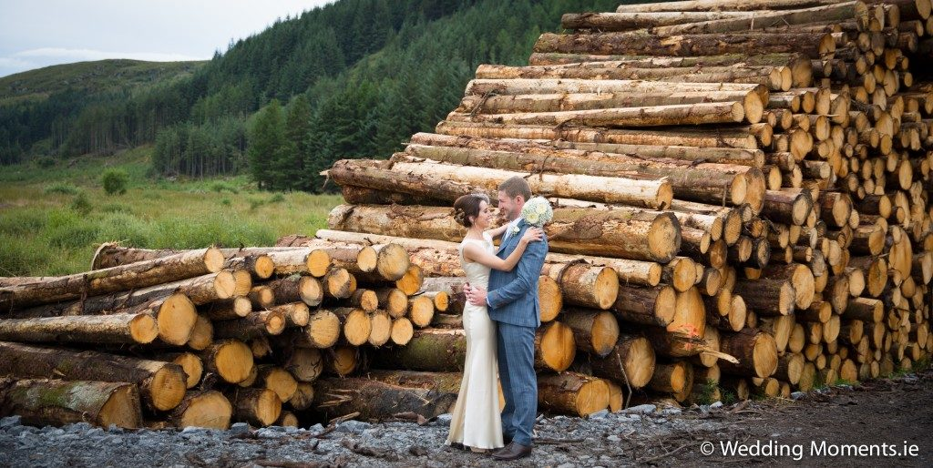 bride and groom standing at logs