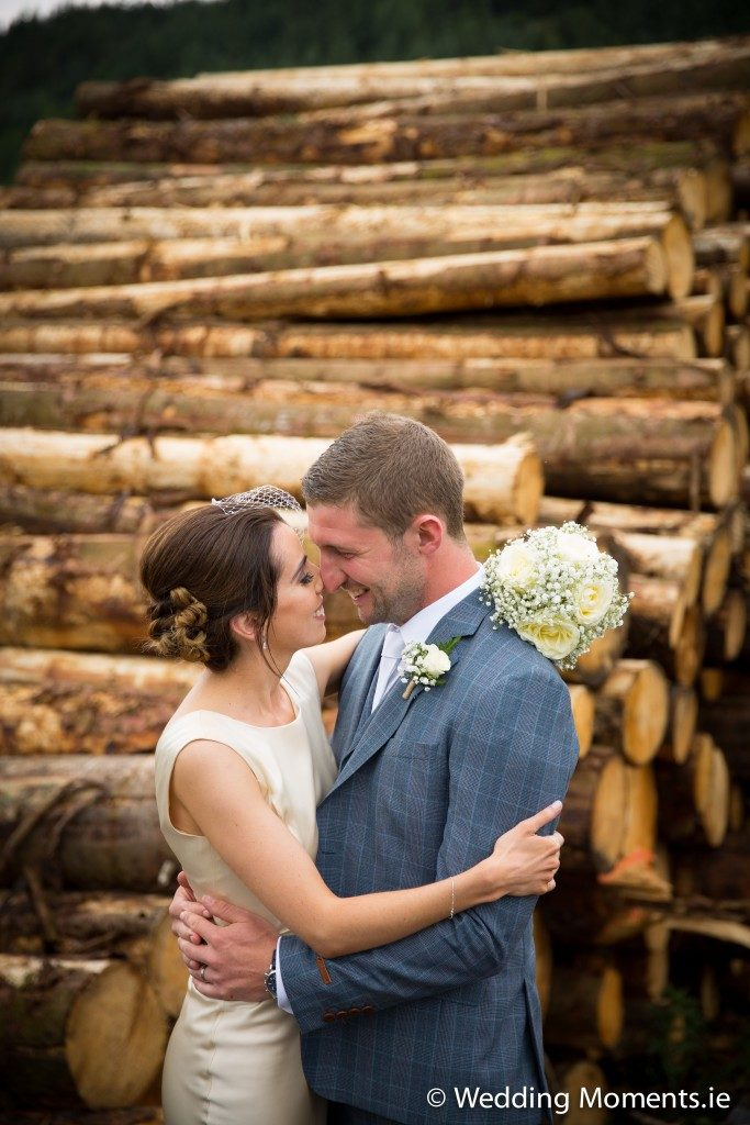 bride and groom with log backdrop