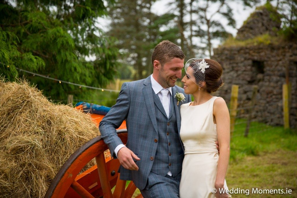 bride and groom smiling at old cart
