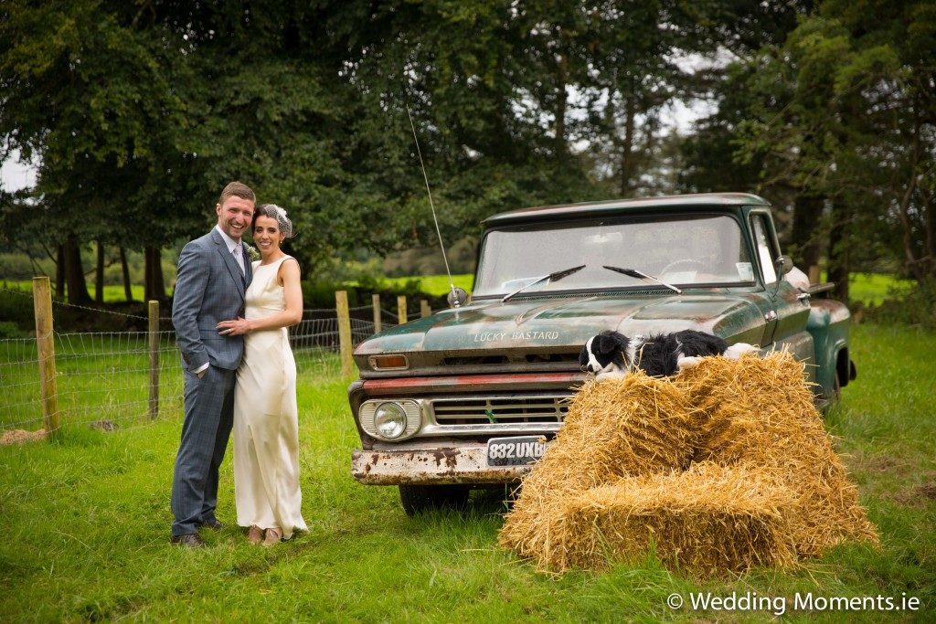 bride and groom standing at funny vintage pickup truck