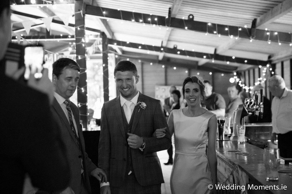 bride and groom entering ballroom