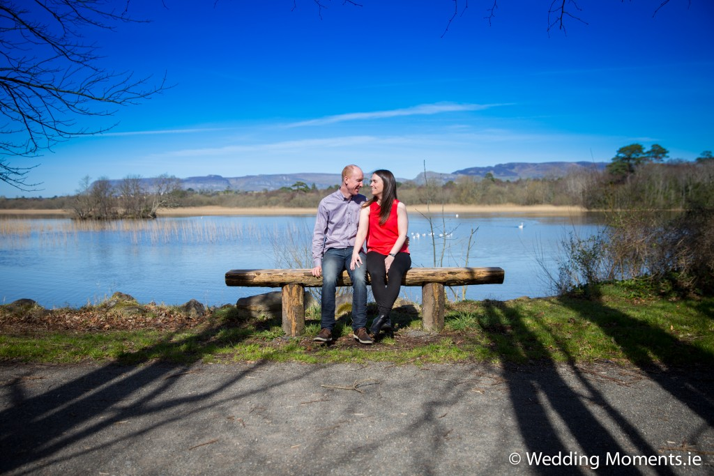 Couple sitting on bench with lake in bakground